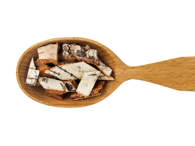 Écorce de bouleau sèche dans une cuillère en bois sur fond blanc.