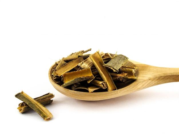 L'écorce de saule sec se trouve dans une cuillère en bois sur fond blanc