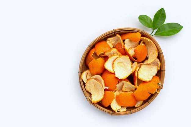 Les écorces d'orange dans un panier en bambou sur une surface blanche