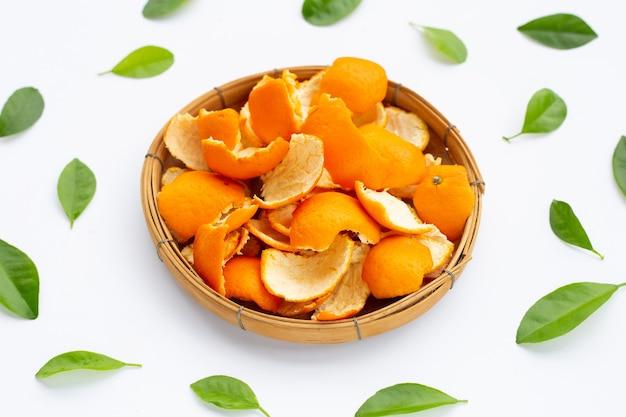 Les écorces d'orange dans le panier sur une surface blanche