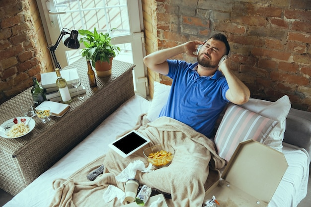 Une écoute joyeuse et inspirée de la musique avec un casque. homme paresseux vivant dans son lit entouré de désordre. pas besoin de sortir pour être heureux. utiliser des gadgets, regarder des films et des séries, émotif. fast food.