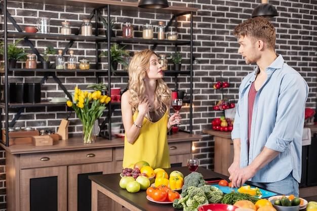 Écouter bien-aimé. mari barbu coupant des légumes et écoutant sa bien-aimée boire du vin rouge