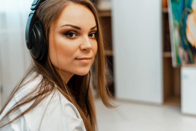 Écouter de la musique. belle jeune fille avec un gros casque sur la tête. fermer. loisirs et musique.
