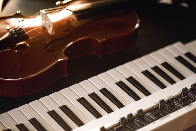 Écouter de la musique classique. vue rapprochée d'un instrument de violon classique allongé sur un synthétiseur. notion musicale. instruments de musique.