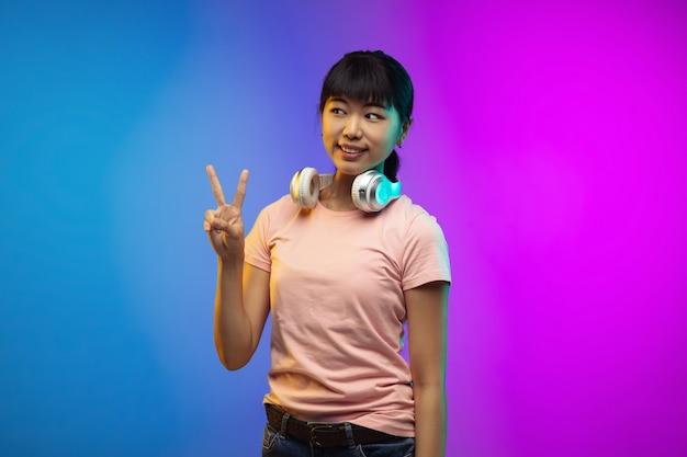 Écouter de la musique, la paix. portrait de jeune femme asiatique sur fond de studio dégradé en néon. beau modèle féminin dans un style décontracté. concept d'émotions humaines, expression faciale, jeunesse, ventes, publicité.