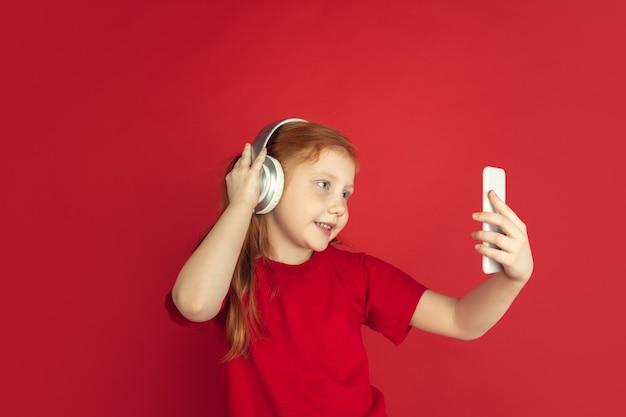 Écouter de la musique. portrait de petite fille caucasienne isolé sur mur rouge. modèle redhair mignon en chemise rouge. concept d'émotions humaines, expression faciale. espace de copie.
