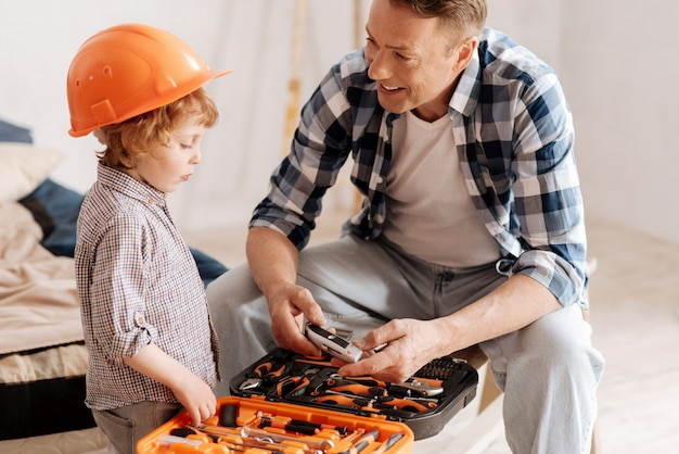 Écouter le père. homme souriant assis sur le banc et tenant l'instrument tout en regardant son fils