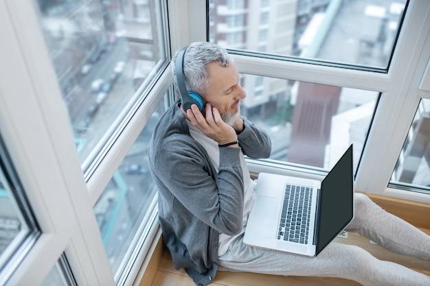 Écouter quelque chose. un homme mûr avec un ordinateur portable et des écouteurs écoutant quelque chose sur internet