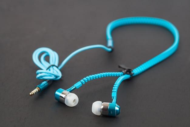 Écouteur bleu et ligne de câble comme fermeture à glissière