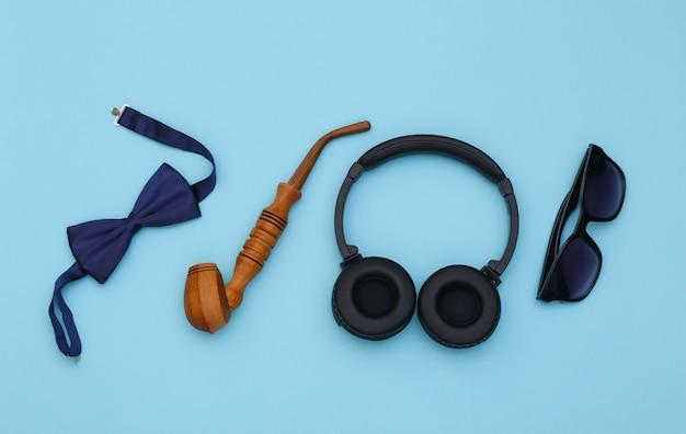 Écouteurs et accessoires de gentleman sur fond bleu. vue de dessus