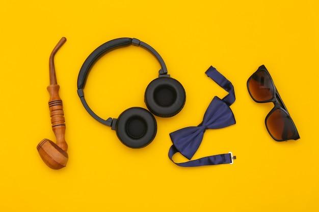 Écouteurs et accessoires de gentleman sur fond jaune. vue de dessus