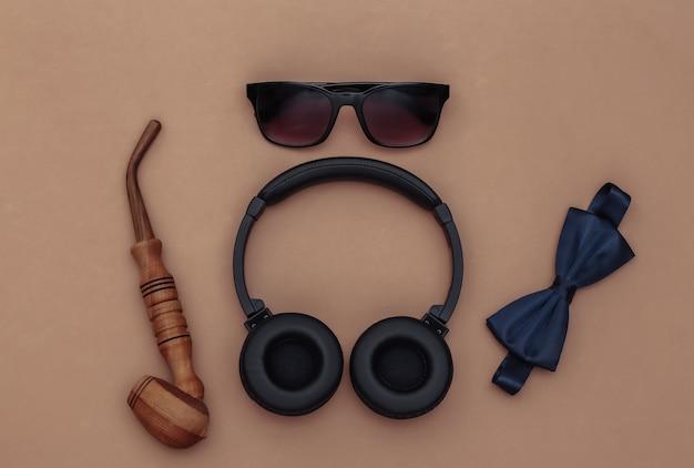 Écouteurs et accessoires de gentleman sur fond marron. vue de dessus
