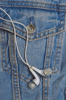 Écouteurs blancs pour le téléphone sur le fond d'une veste en jean. fermer.