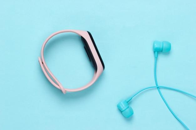 Écouteurs avec bracelet intelligent sur bleu pastel