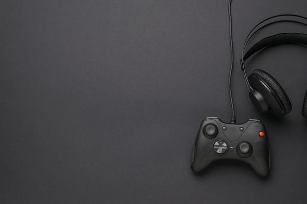 Des écouteurs et une console de jeux sur fond noir. un appareil pour jouer à des jeux informatiques. mise à plat. place pour le texte.