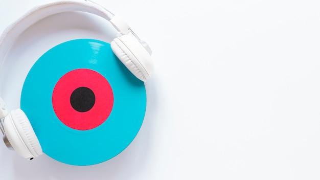 Écouteurs et disque vinyle sur fond uni