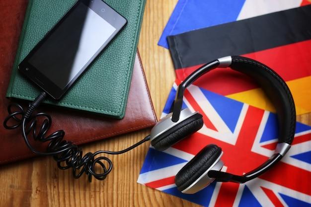 Écouteurs et drapeau sur une langue de cours de concept de fond en bois