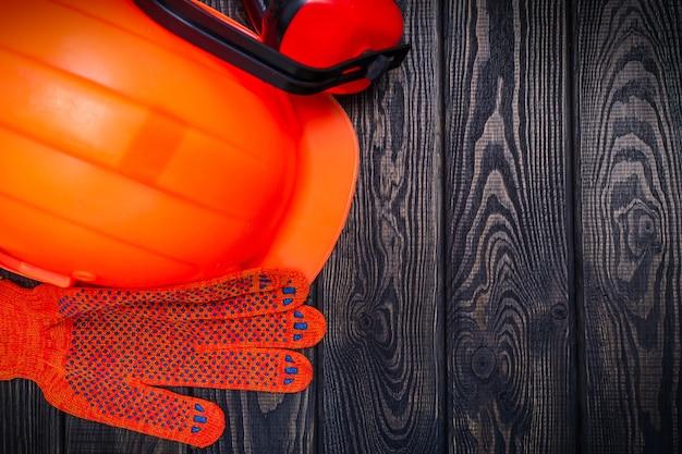 Écouteurs et gants oranges de casque sur un fond foncé en bois équipement de protection pour le constructeur