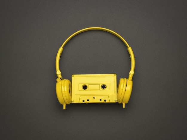 Des écouteurs et un magnétophone sur fond noir. tendance de couleur. mise à plat.