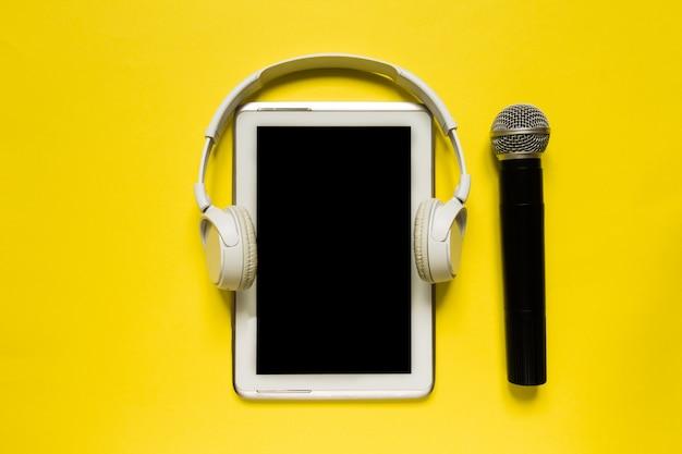 Des écouteurs modernes et une tablette blancs sur fond jaune et plat, vue de dessus, à l'arrière-plan jaune tendance pour texte