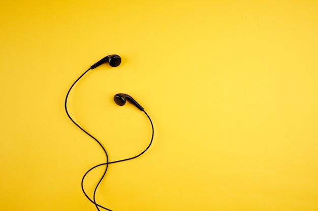 Écouteurs noirs sur jaune chaud à la mode. concept de style de vie de musique. copie espace. pose à plat