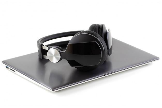 Des écouteurs noirs se trouvent sur un ordinateur