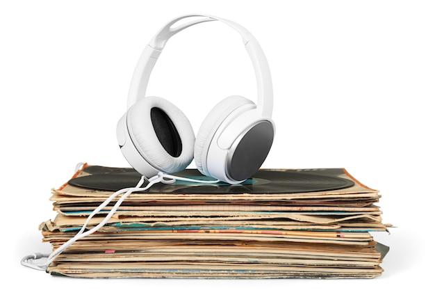 Écouteurs d'or se trouvant sur la pile de disques vinyle