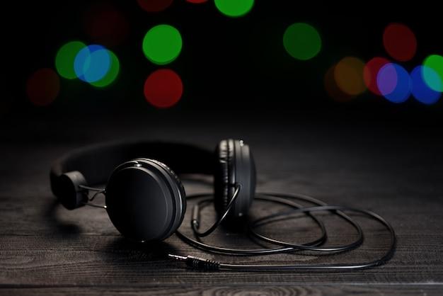 Écouteurs pour jeux informatiques. les écouteurs sont de couleur sombre contre un mur en bois.