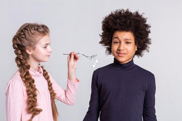 Écouteurs roulés. garçon à l'incompréhension tandis qu'une fille portant une fourchette avec des écouteurs blancs attachés