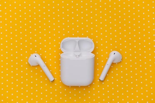 Écouteurs sans fil blancs avec étui de chargement sur fond pointillé jaune.