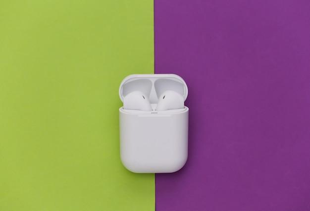 Écouteurs sans fil blancs avec étui de chargement sur fond violet vert.