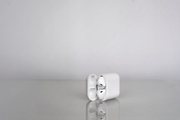 Écouteurs sans fil avec une boîte de chargement sur fond gris avec reflet dans le verre