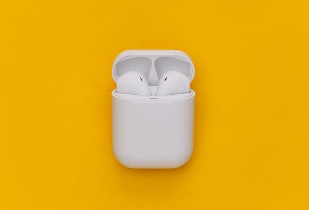 Écouteurs sans fil modernes avec étui de chargement sur fond jaune.