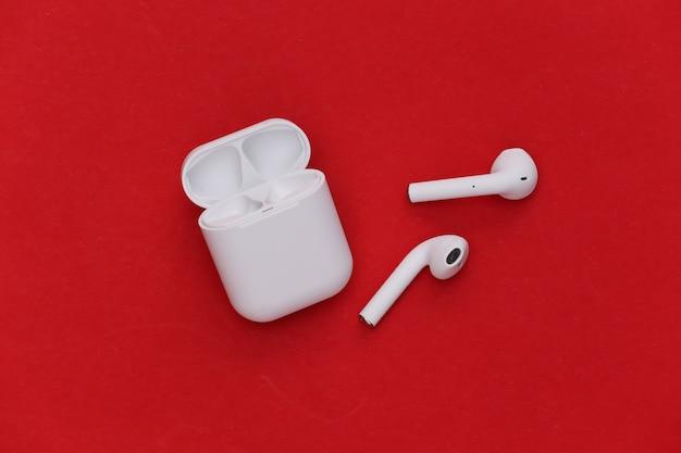 Écouteurs sans fil modernes avec étui de chargement sur fond rouge.