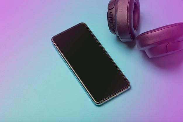 Les écouteurs avec smartphone simulent des écouteurs audio sonores sur un fond néon coloré avec un blanc ...
