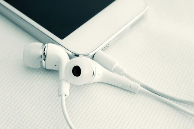 Écouteurs et téléphone portable sur fond de table blanche