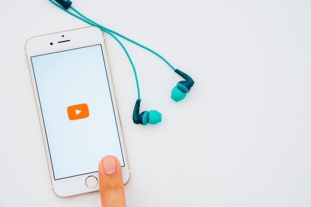 Écouteurs et téléphone touchant le doigt avec l'application youtube