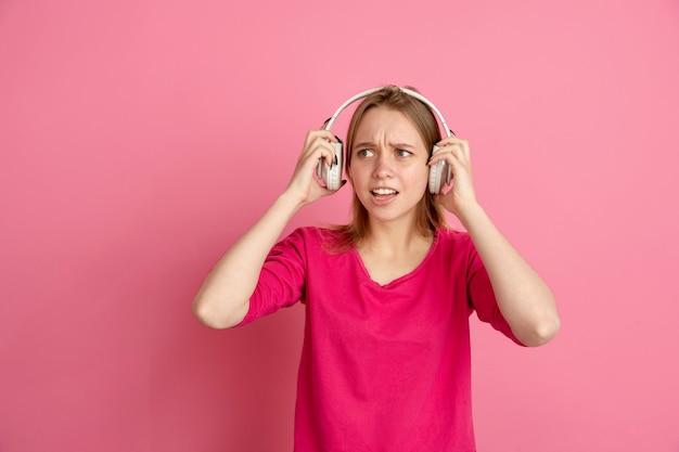 Écoutez de la musique, choqué. portrait de jeune femme caucasienne isolé sur mur rose, monochrome. beau modèle féminin. concept d'émotions humaines, expression faciale, ventes, publicité, tendance.