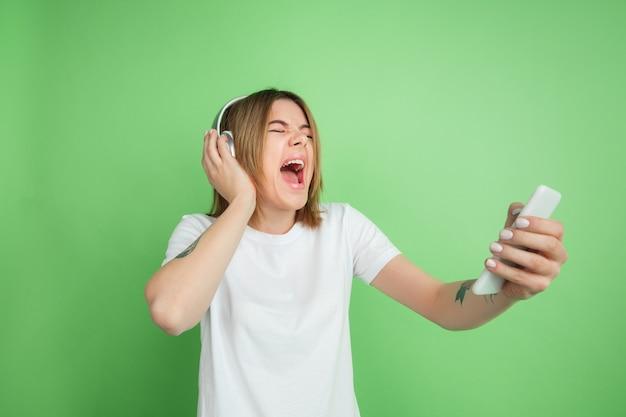 Écoutez de la musique, criez. portrait de jeune femme caucasienne isolé sur mur vert. beau modèle féminin en chemise blanche. concept d'émotions humaines, expression faciale, jeunesse.