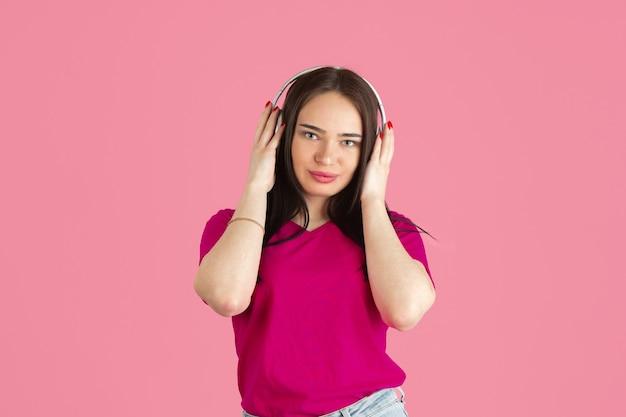 Écoutez de la musique. portrait monochrome de jeune femme brune caucasienne isolée sur le mur rose du studio.