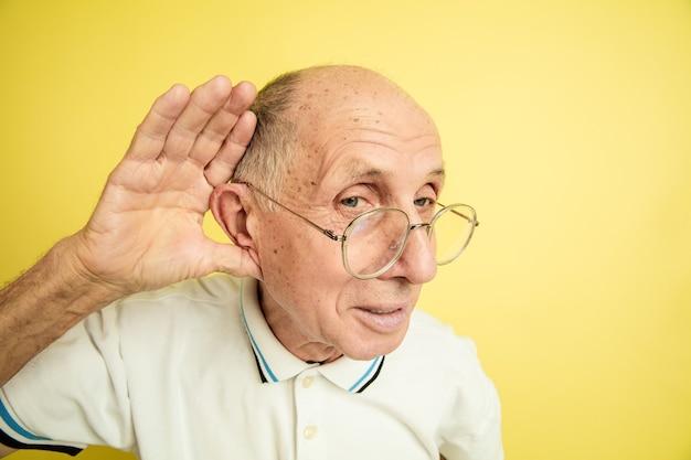 Écoutez les secrets. portrait de l'homme senior caucasien isolé sur fond de studio jaune. beau modèle émotionnel masculin. concept d'émotions humaines, expression faciale, ventes, bien-être, publicité. copyspace.