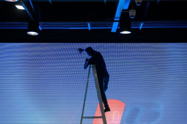 Écran d'affichage numérique pendant la maintenance par un technicien, liste de contrôle de maintenance vierge pour le panneau d'affichage numérique