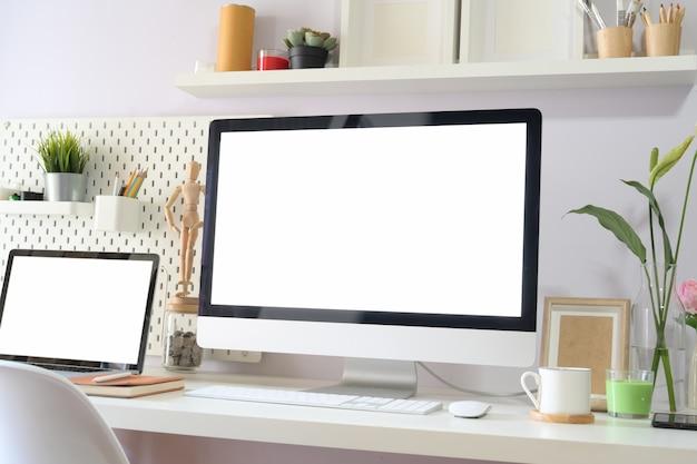 Écran blanc maquette d'ordinateur dans l'espace de travail loft