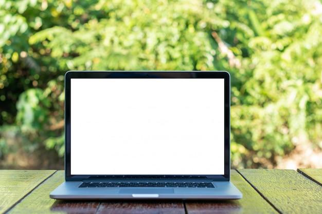 Écran blanc de l'ordinateur portable sur une table en bois