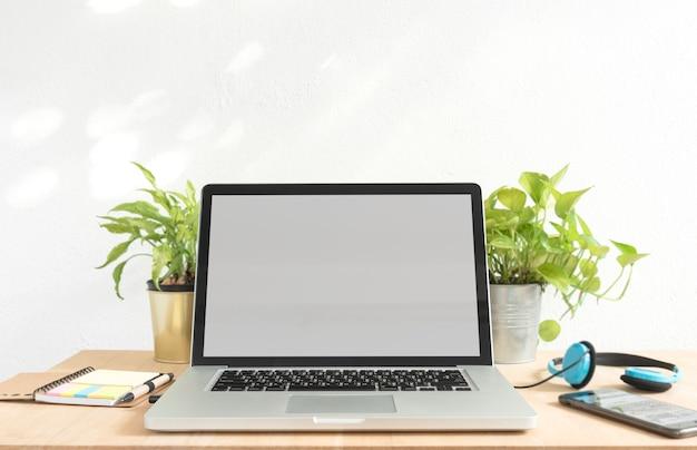 Écran blanc pour ordinateur portable pour modèle de technologie de conception créative maquette sur table en bois.