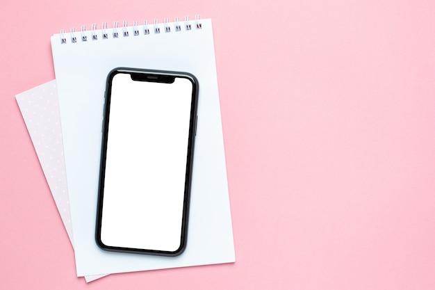 Écran blanc de téléphone portable et cahier d'affaires rose avec espace copie