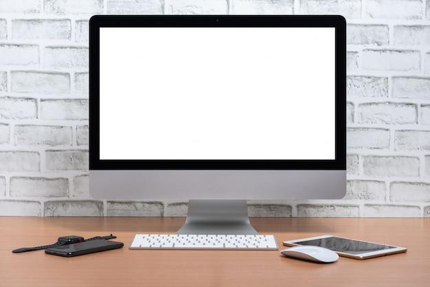 Écran blanc de tout en un ordinateur avec tablette, téléphone intelligent et montre intelligente sur une table en bois, fond de mur de briques blanches