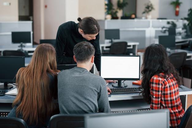 Écran de couleur blanche. mettez votre texte là-bas. groupe de jeunes en vêtements décontractés travaillant dans le bureau moderne