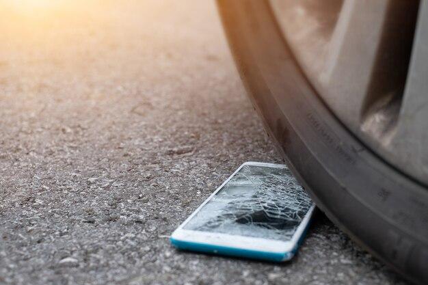 L'écran du smartphone est fissuré à plat sur la route à cause du déplacement d'un pneu de voiture à l'avant
