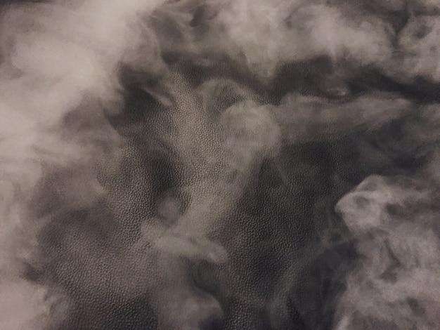 Écran de fumée sur un fond en cuir noir qui crée un léger aspect granuleux.